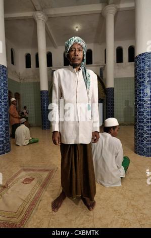 Spiritual leader Kyai-Haji Abdurrahman, 57, poses in the mosque at Al-Bajigur Mental Asylum and Religious Boarding - Stock Photo