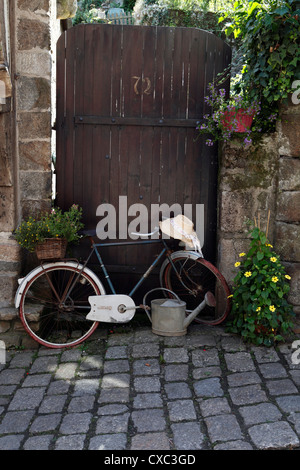 Bike with flowers in the basket propped up against a garden gate in Dinan, France. - Stock Photo