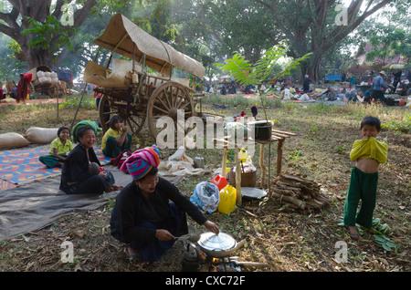 Pa Oh minority women and children cooking next to their bull cart, Kakku festival, Shan State, Myanmar (Burma), - Stock Photo