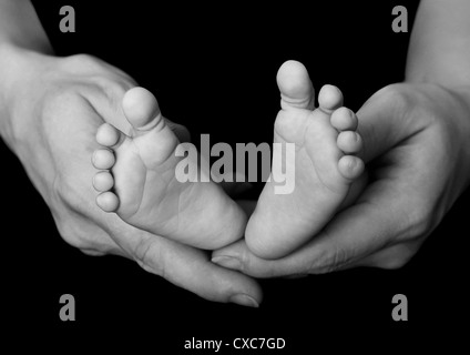 Young baby's feet in her mother's hands - Stock Photo