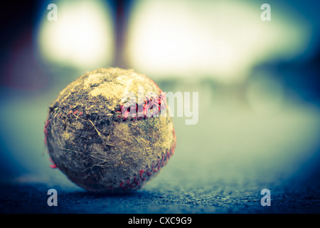 Grungy well worn old baseball on ground with very shallow depth of field.  Toned Image - Stock Photo