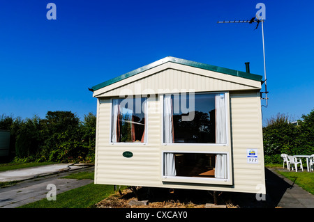 The early morning sun reflects brightly off the front of a cream holiday caravan contrasting with an intensely blue - Stock Photo