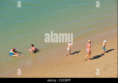 Elderly aged women bathing in sea and sunbathers, mother with children, walking on beach in summer, Charente Maritime, - Stock Photo