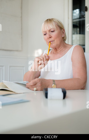 mature caucasian woman checking bills and doing budget at home - Stock Photo