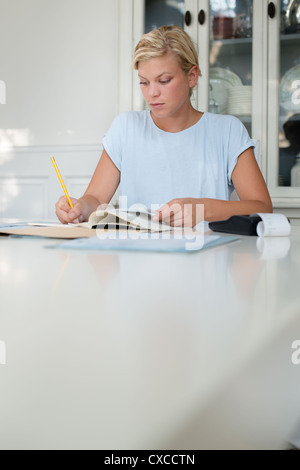 young blond woman checking bills and using calculator at home - Stock Photo