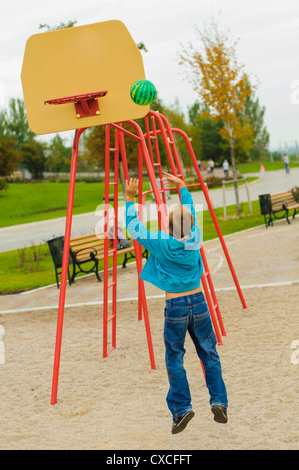 Young boy playing basketball at outdoors playground - Stock Photo
