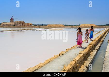 Three girls walking along the salt pans in Laguna dello Stagnone near Trapani, Sicily, Italy - Stock Photo
