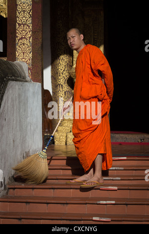 Buddhist monk cleaning the stairs in front of a temple, Chiang Mai, Thailand - Stock Photo