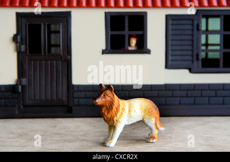 Concept photo: A toy guard dog guarding a house while a toy man watch out from his home window. - Stock Photo