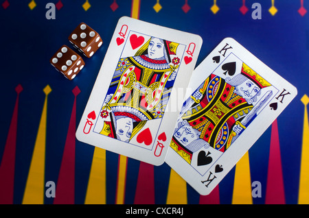 Queen and King playing cards with dice on a colorful casino table surface. - Stock Photo