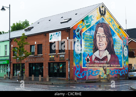 Sinn Fein constituency office with mural of Bobby Sand on Catholic Falls road, Belfast in Northern Ireland. - Stock Photo