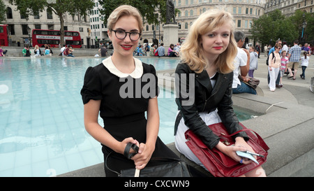 Two teenage girls in vintage clothing, black dress collar, & handbags sitting by fountain in summer Trafalgar Square London England UK   KATHY DEWITT