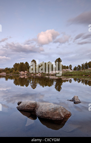 Clouds at sunset reflected in an unnamed lake, Shoshone National Forest, Wyoming, United States of America, North - Stock Photo