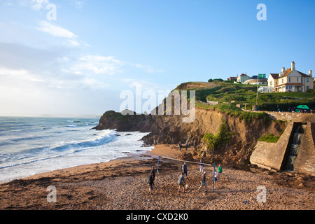 Tourists play volleyball in the evening light on Shippen beach at Outer Hope, Hope Cove, South Hams, Devon, England, - Stock Photo