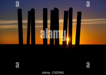 Sunrise seen through a sculpture over the Mediterranean sea. - Stock Photo