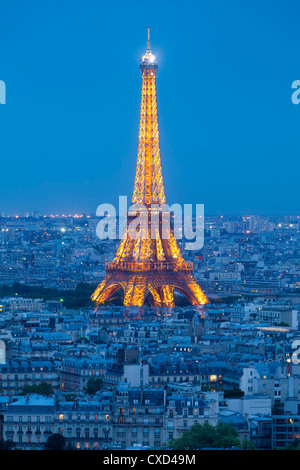 Illuminated Eiffel Tower, viewed over rooftops, Paris, France, Europe - Stock Photo