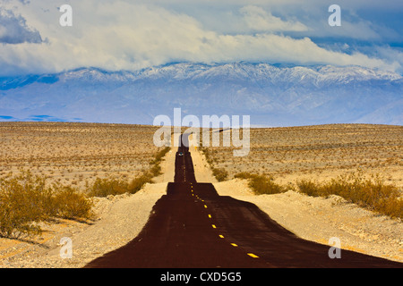Traveling down the road in desert - Stock Photo