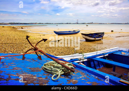 Old blue fishing boats in a beach and rusty anchor in the foreground - Stock Photo