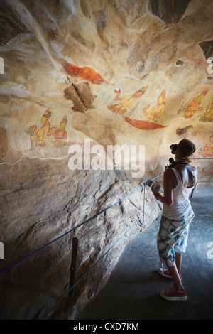 Tourist taking photos of ancient frescoes, Sigiriya, UNESCO World Heritage Site, North Central Province, Sri Lanka, - Stock Photo