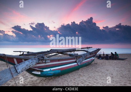 Oruwa (outrigger canoe) on beach at sunset, Negombo, North Western Province, Sri Lanka, Asia - Stock Photo