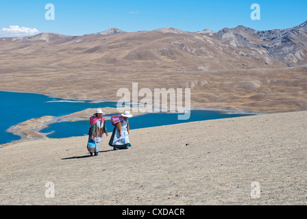 Aymara women in the Cordillera Real with the Lake Tuni in the background - Stock Photo