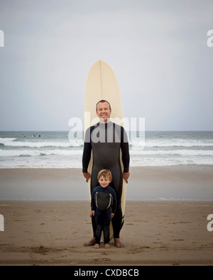 Caucasian father and son in wetsuits with surfboard - Stock Photo