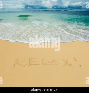relax written in a sandy tropical beach - Stock Photo