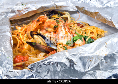 pasta with oysters and tomato in foil - Stock Photo