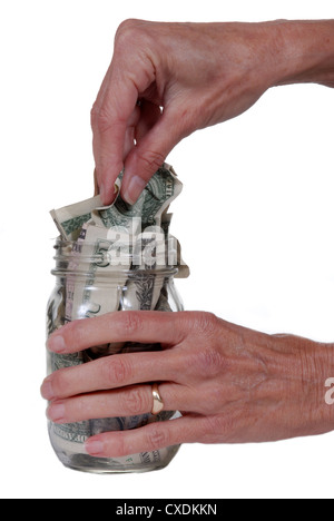 Female hand taking dollar bills out of glass jar. Isolated on white. - Stock Photo