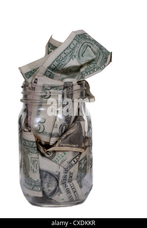 A glass jar stuffed with dollar bills. Isolated on white. - Stock Photo