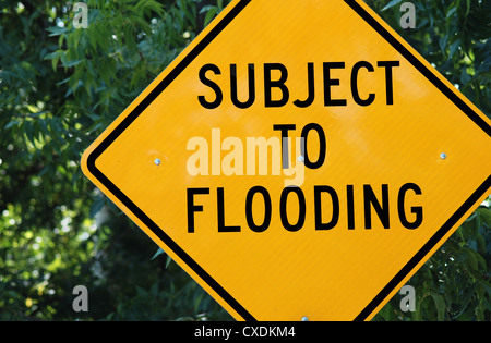Yellow warning sign which reads: 'Subject to Flooding' - Stock Photo
