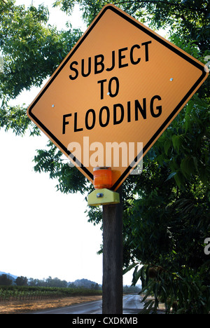 Yellow warning sign on the side of a rural lane: 'Subject to Flooding' - Stock Photo