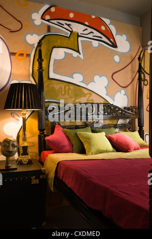 Antique objects set against bold 21st century graffiti wall decoration - Stock Photo