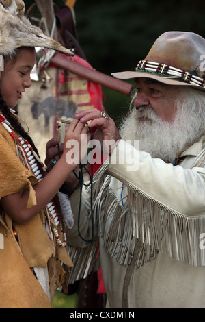 A young Native American Indian boy playing with an antler bone whistle gift from a mountainman - Stock Photo