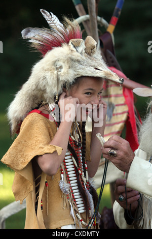 A young Native American Indian boy plugging his ears from a loud noise from a antler bone whistle - Stock Photo