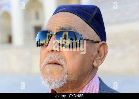 The Kalon mosque in Bukhara reflected on an Uzbek's man sunglasses. - Stock Photo
