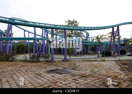 It's a photo of a Roller Coast in an abandoned entertainment park somewhere in Thailand, Asia. It's Purple and green - Stock Photo