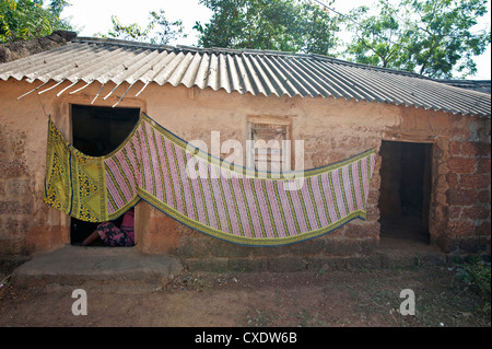 Cotton sari being hung out to dry across village house wall, rural Orissa, India, Asia - Stock Photo