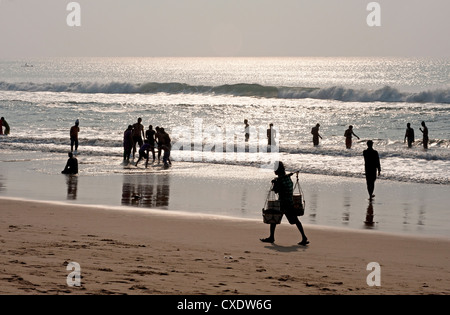 Puri beach on the Bay of Bengaln families relaxing and paddling, beach vendor walking by in the late afternoon, - Stock Photo