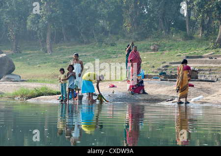 Women washing clothes on the ghats of the  River Mahanadi, reflected in the water, Orissa, India, Asia - Stock Photo