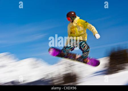 Snowboarder flying off a ramp, Whistler Mountain, Whistler Blackcomb Ski Resort, Whistler, British Columbia, Canada - Stock Photo