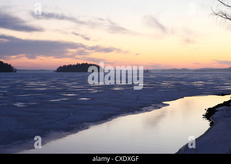 Sunset over the mainly frozen surface of Lake Pyhajarvi, the ice surrounds islands, at Tampere, Pirkanmaa, Finland, - Stock Photo