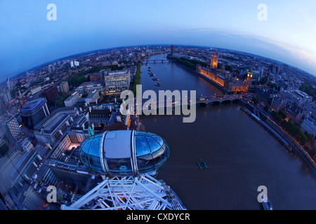 View of passenger pod capsule, Houses of Parliament, Big Ben and the River Thames from the London Eye at dusk, London, England