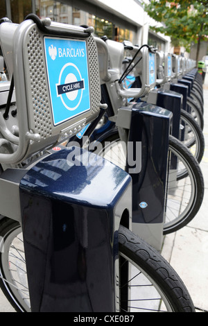 A row of 'Boris Bikes' docked in a Barclays Cycle Hire docking Station on Baker Street. - Stock Photo