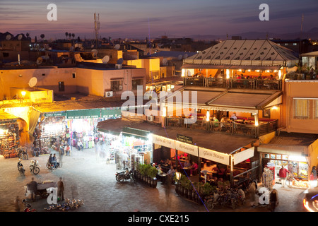 View over market square at dusk, Place Jemaa El Fna, Marrakesh, Morocco, North Africa, Africa - Stock Photo