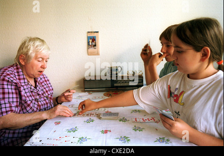 Berlin, a grandmother and granddaughter playing with grandchildren cards at the kitchen table - Stock Photo