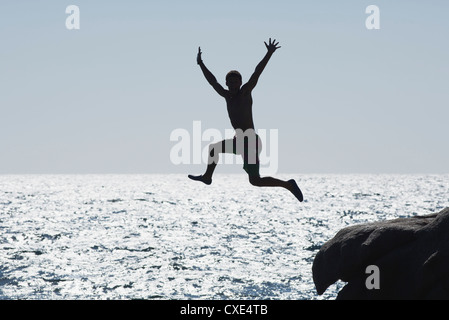 Teenage boy jumping into ocean, silhouette - Stock Photo