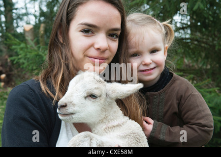 Teenage girl and little sister with pet lamb, portrait - Stock Photo