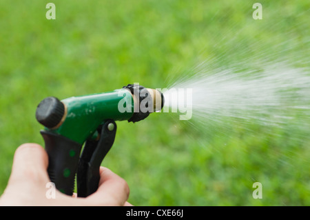 Person using spray nozzle on garden hose to water lawn, cropped - Stock Photo