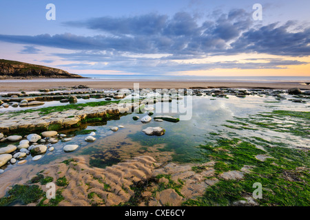 Sunset over rocks and pools at Dunraven Bay, Southerndown, Wales - Stock Photo